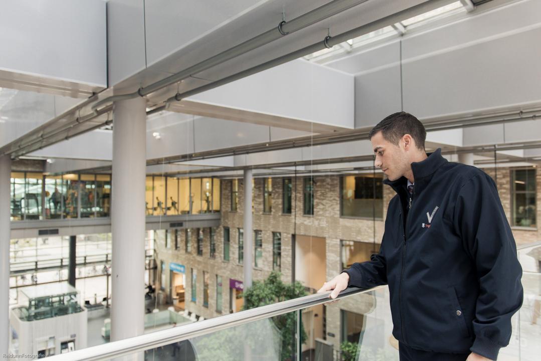 Foto van een beveiliger van Trigion die in een kantoor over de balustrade naar beneden kijkt