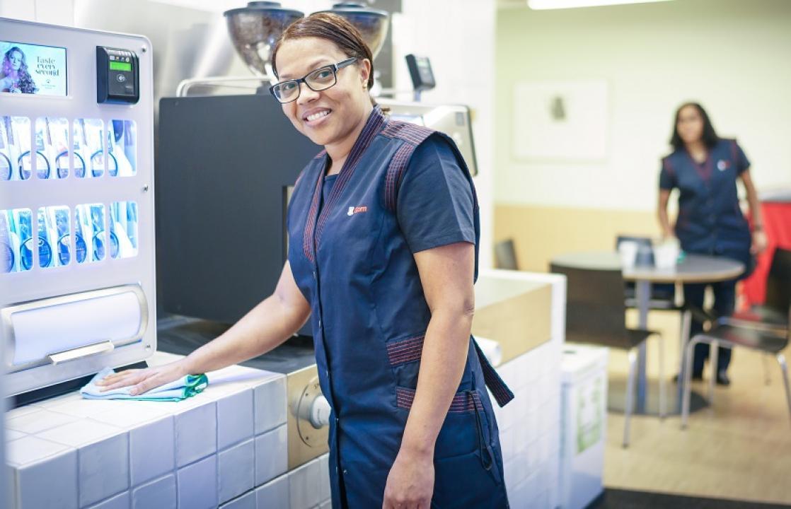 Foto van dame met bril die schoonmaakt in een bedrijfsrestaurant terwijl ze naar de camera kijkt