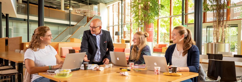 Studenten aan tafel in gesprek met medewerker van Gom