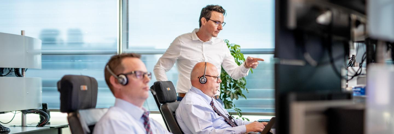 Twee mannen kijken op een computerscherm om op afstand bruggen, wegen en sluizen te bedienen.