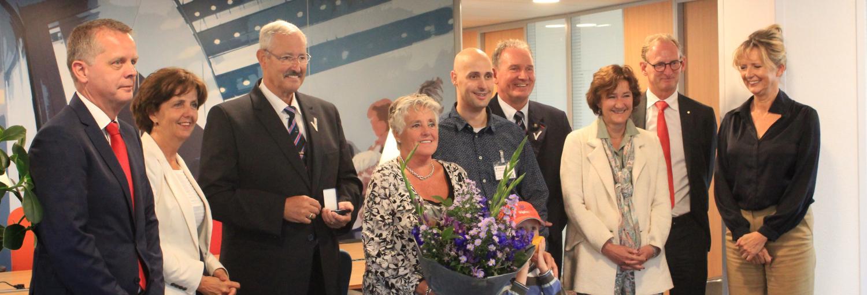 Vijf mannen en vier vrouwen staan op het hoofdkantoor van Trigion met elkaar op de foto om het jubileum van een medewerker te vieren.