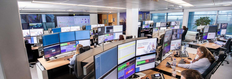 Een overview van de AlarmServiceCentrale waarin centralisten op beeldschermen de inkomende meldingen behandelen.