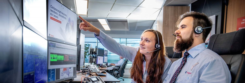 Twee centralisten bekijken de inkomende meldingen op het beeldscherm op de AlarmServiceCentrale.