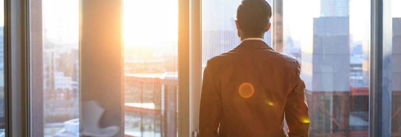 Man in zakelijke kleding kijkt uit het raam van zijn kantoor.