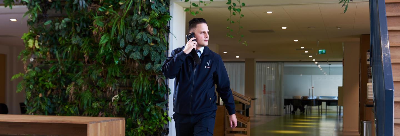 Mannelijke beveiliger loopt in zijn uniform door gang met een groene omgeving en belt met de centrale over de ingekomen melding via een portofoon.