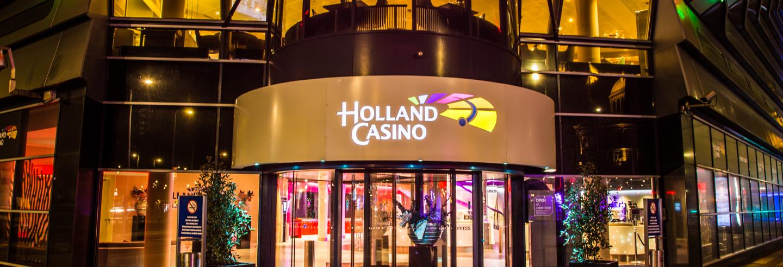 De voorkant van een Holland Casino waarbij je kijkt op de draaideur met daarboven het logo.