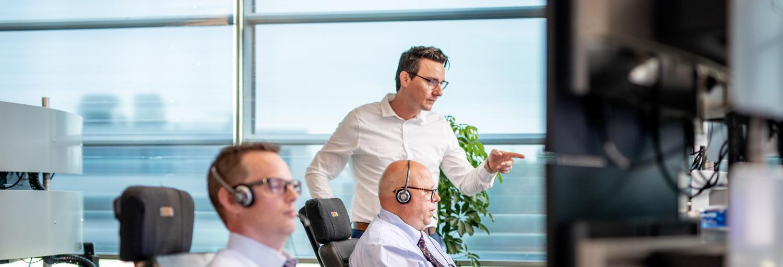 Op de AlarmServiceCentrale bekijken twee mannelijke centralisten de inkomende meldingen op het beeldscherm.