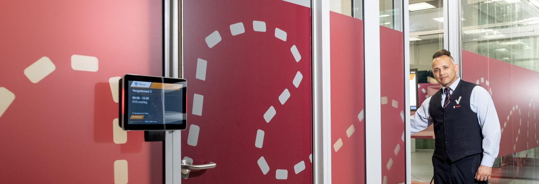 Mannelijke beveiliger in uniform loopt op het Albeda College een ronde en opent een glazendeur van een klaslokaal om te controleren of iemand aanwezig is in het lokaal.