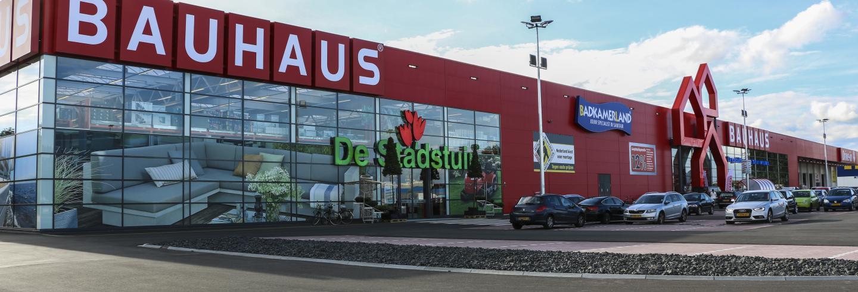 Voorkant van een vestiging van BAUHAUS. Een glazen muur met daarboven een rode gevel met het logo.