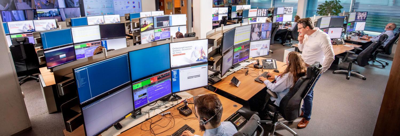 Trigion collega's die toezicht houden op de actuele situatie door te kijken naar zes verschillende beeldschermen.