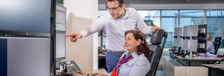 Man staat naast vrouwelijke Trigion collega die haar ondersteunt in haar werk.
