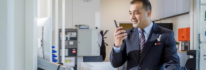 Mannelijke beveiliger in uniform praat via de portofoon met een collega beveiliger op locatie en kijkt daarnaast ook gelijk op zijn computerscherm achter zijn bureau.