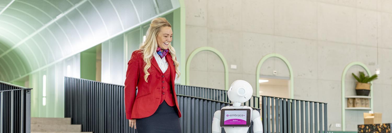 Gastvrouw  in uniform staat naar robot in centrale hal van een kantoorpand.