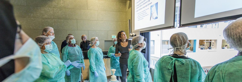 medewerkers van Gom Zorg met beschermkleding aan, schort, mondkapje en haarnetje, luisteren naar docent infectiepreventie