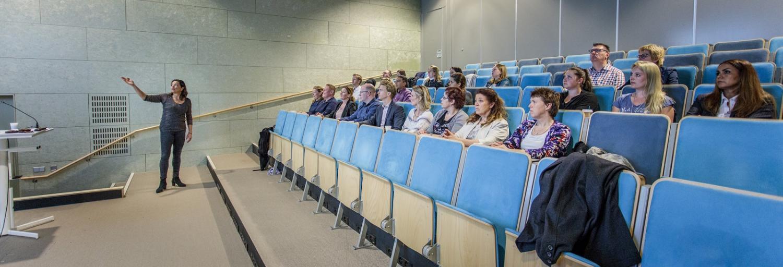 medewerkers van Gom Zorg zitten te luisteren naar docent infectiepreventie