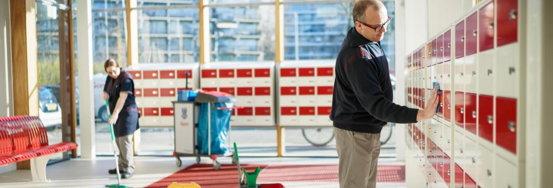 2 medewerkers van Gom Openbare Ruimten maken de entreehal van een flat schoon, de een wist de vloer de ander het postvakjestableau