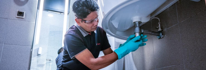 een medewerker van Gom Specialistische Reiniging maakt het sifon van een wastafel schoon tijdens een dieptereiniging sanitair