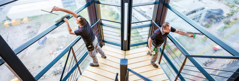 2 medewerkers van Gom Specialistische Reiniging zemen de ramen in een trappenhuis met hele hoge ramen