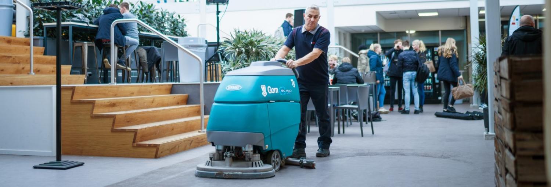 een medewerker van Gom is met een schrobzuigmachine de vloer aan het reinigen in een schoolpand