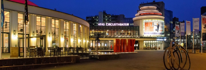 het Afas Circustheater in de avond met alle lichtjes aan en op het billboard de reclame voor de BIlly Elliot musical