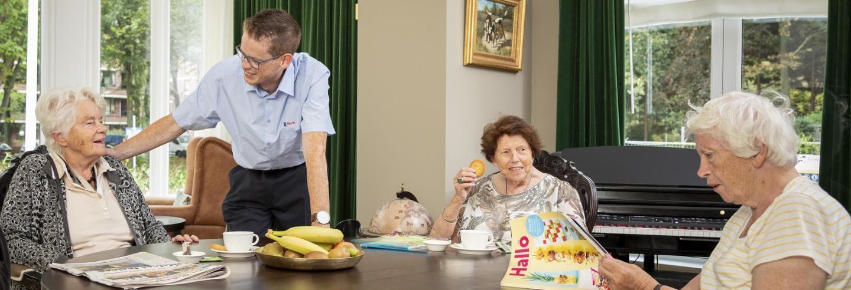 drie bejaarden vrouwen zitten aan tafel met een kopje koffie en een koekje en een schoonmaakmedewerker van Gom maakt met hen een praatje