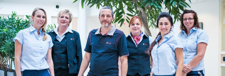 een groepsfoto van medewerkers van Gom Zorg, lachend kijkend in de camer