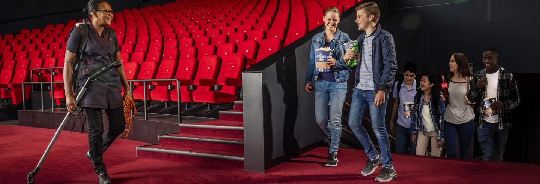 de schoonmaakster van Gom verlaat de bioscoopzaal, terwijl er nieuwe bezoekers de zaal binnenlopen