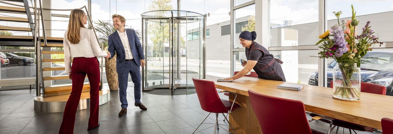 een bezoeker komt een bedrijfspand binnen en wordt verwelkomd door een medewerker en ze schudden de hand, ondertussen is een schoonmaakmedewerkster van Gom de leestafel aan het schoonmaken.