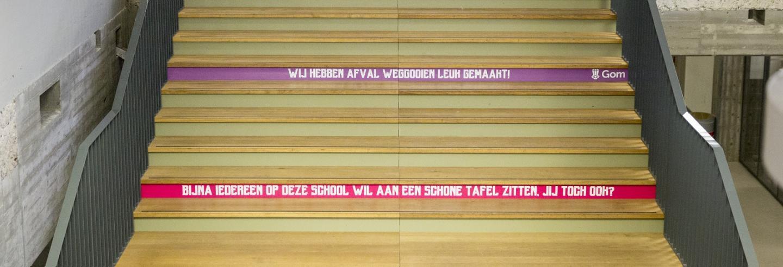een brede houten trap in een school met op 2 achterborden teksten als 'Wij hebben afval weggooien leuk gemaakt!' en 'Bijna iedereen op school wil aan een schone tafel zitten, jij toch ook?'
