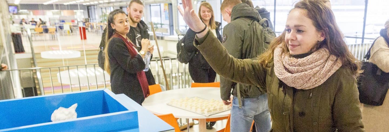 een studente gooit met een boogje een propje papier in de trash roulette, de interactieve afvalbak van Gom Onderwijs, op de achtergrond kijken studenten mee