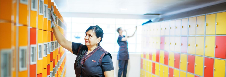 een medewerkster van Gom Onderwijs maakt met een blauw doekje de deurtjes van de lockers in school school, op de achtergrond is een schoonmaakster van Gom bezig met de bovenkant van de lockers schoon te maken.