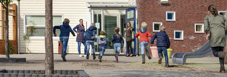 een groepje basisschool-kinderen rennen naar de deur van de school waar zowel de juf als de schoonmaakster van Gom ze staat op te wachten