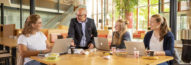 drie studenten aan het werk zittend aan een tafel in de aula en kijken naar een schoonmaakmedewerker van Gom die hen aanspreekt.