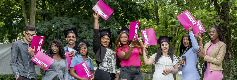 een uitbundige groep geslaagde studenten van Zadkine die hun diploma juichend omhoog houden