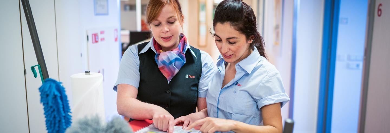 een leidinggevende van Gom Zorg legt een schoonmaakmedewerkster uit wat ze moet door te wijzen op de taakkaart