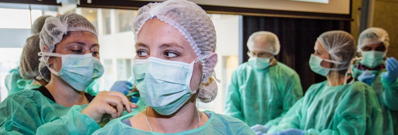 een vijftal personen met groene medische beschermkleding en mondkapjes en haarnetjes, waarbij 1 persoon de andere helpt met het vastknopen van het schort in de nek