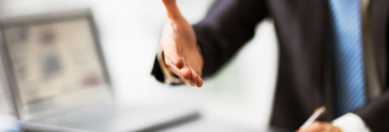 Man in zakelijke kleding steekt hand uit naar zijn gesprekspartner.