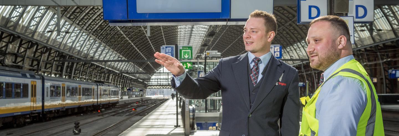 Mannelijke beveiliger in uniform legt aan mannelijke beveiliger met een veiligheidshesje uit wat de situatie is. Zij staan samen op het perron van een treinstation.