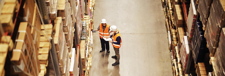 Een groot magazijn met voorraad op enorme schappen met daarnaast twee medewerkers die in gesprek zijn met elkaar