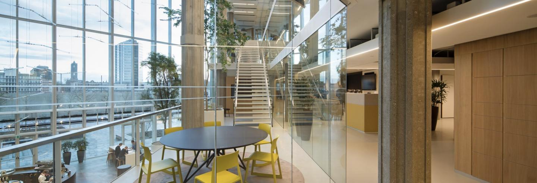 Moderne ontvangstruimte omgeven door hoge glazen puien die uitzicht bieden op de stad