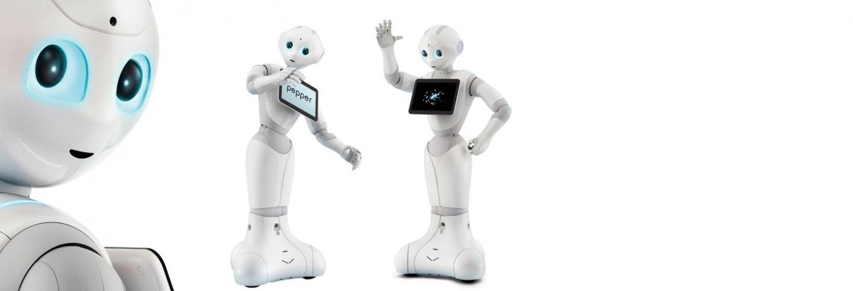 Drie witte robots met blauwe ogen genaamd Pepper, zij hebben een iPad voorop voor informatie op te lezen.