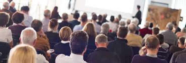 Een zaal vol met mensen in zakelijke kleding die luisteren en kijken naar een presentatie.