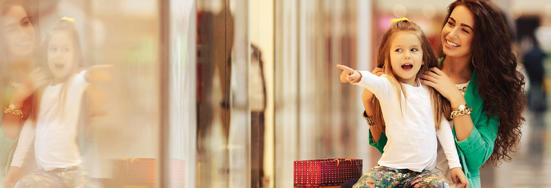 Vrouw lmet jonge dochter aan het winkelen in overdekt winkelcentrum
