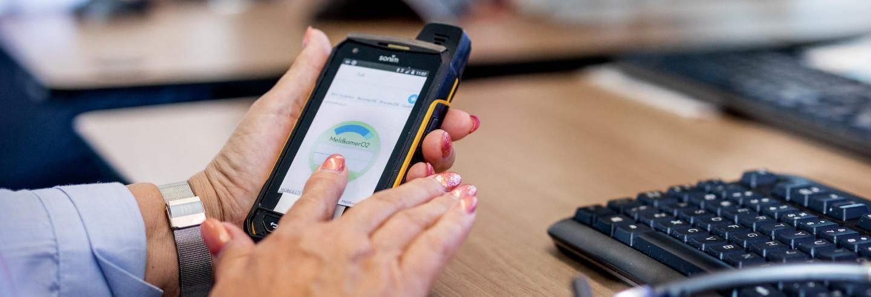 Vrouwlijke Trigion collega die een telefoon vast heeft waar ze Track en Trace op volgt.