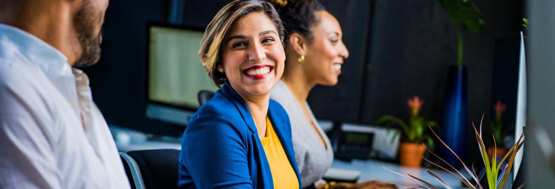 Een man en twee vrouwen zitten naast elkaar aan een bureau achter de computer, de focus ligt op een vrouw met een blauw jasje en een geel shirt.