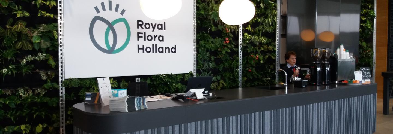 Afbeelding van de receptie in de vorm van een lange bar met daarachter een scherm met de naam Royal Flora Holland