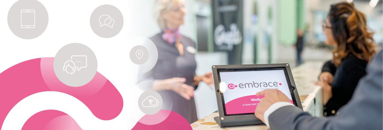 Je ziet de hand van een bezoeker die zich aanmeldt op een tablet met daarop het logo van Embrace. Achter de tablet zie je een Embrace-medewerkster in gesprek met een bezoeker.