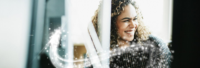 Een jonge dame in een zakelijke omgeving lacht opzij en er is een glitter swoosh te zien.