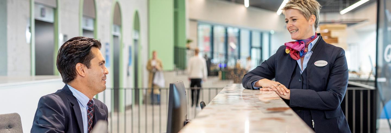 Mannelijke receptionist in uniform zit achter de balie en praat met een gastvrouw in uniform aan de andere kant van de balie.