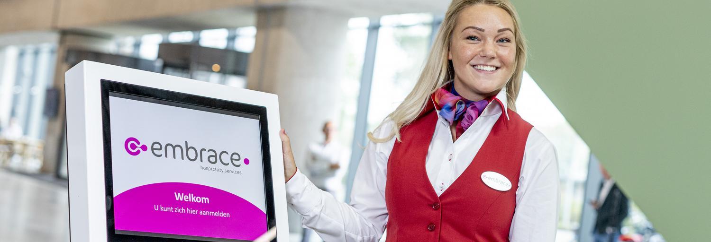 Gastvrouw in uniform staat bij aanmeldpilaar om de bezoeker te helpen met het aanmelden.